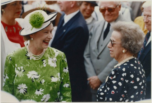 Colour photograph of Queen Elizabeth II in a crowd, smiling.