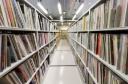 Colour photograph of stacks. There is an aisle down the middle with rows of books on either side.
