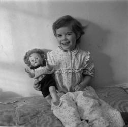 Photograph of a girl sitting on a mattress, holding a doll.