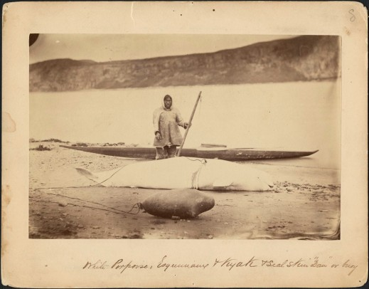 "Portrait of a hunter, a beluga, a seal skin ""daw"" (a buoy), and a kayak along the edge of the Little Whale River, Quebec. Photographer: George Simpson McTavish (MIKAN 3264747)"
