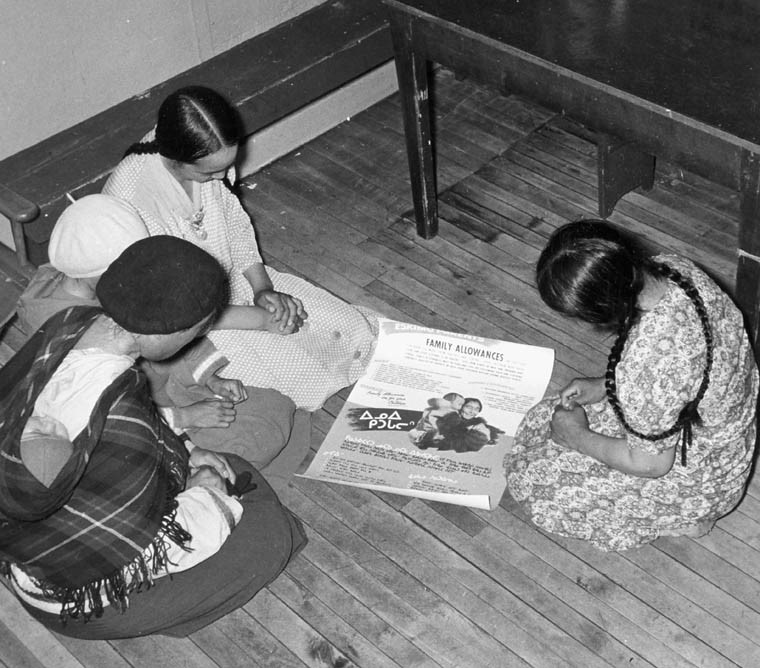 Women looking at a family allowance poster, Baker Lake (Qamanittuaq), Nunavut, by unknown photographer, Health and Welfare Canada (MIKAN 3613868)