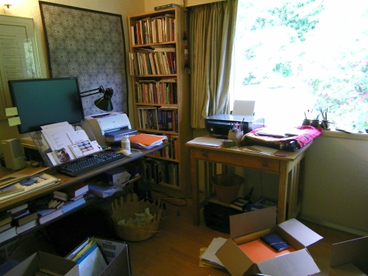 A photograph of P.K. Page's computer desk holding her various papers, books and mementos