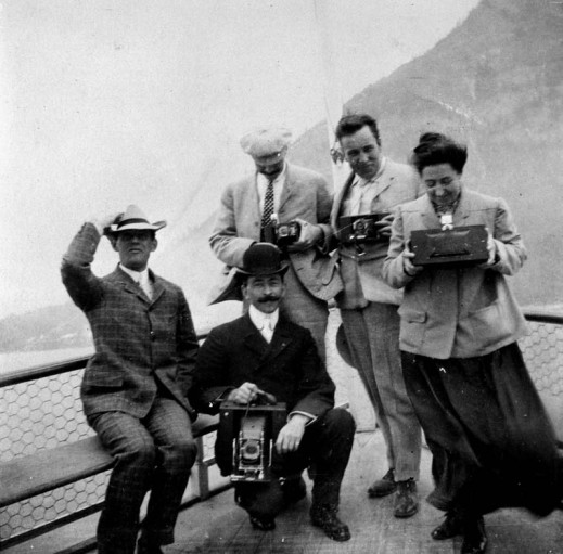 Possibly members of the Benjamin Low family on a passenger steamer showing various types of cameras, including a panoramic camera, 1904.