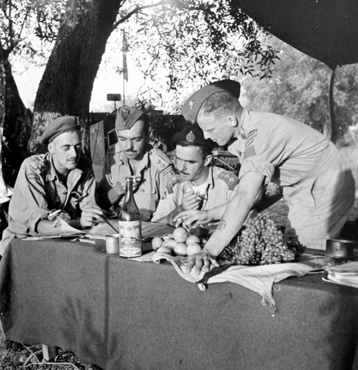 Black and white photograph of four men at a table—three sitting and one standing—intently examining documents, each with a cigarette in hand; a wine bottle and different fruits are prominently displayed on the table.