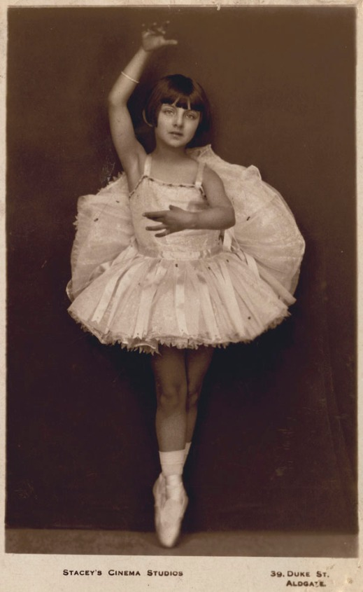A black-and-white studio portrait of Celia Franca as a young girl. She is dressed in a tutu and is on pointe.
