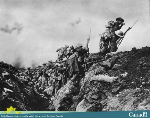 Black and white photograph showing soldiers climbing over a ridge.