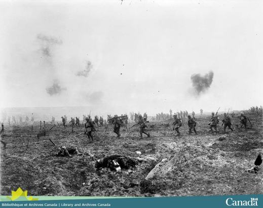 Black and white composite photograph of soldiers advancing through a field of mud. There's puffs of smoke in the air and bodies in the foreground.