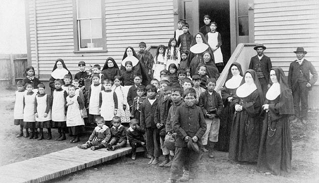 Black and white photograph of a group of Indigenous girls and boys, nuns and two men posing in front of a building
