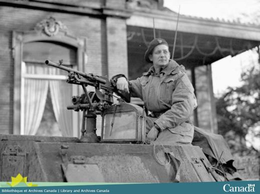 Black and white photograph showing a man sitting on top of a tank, leaning against the machine gun and looking off to the left.