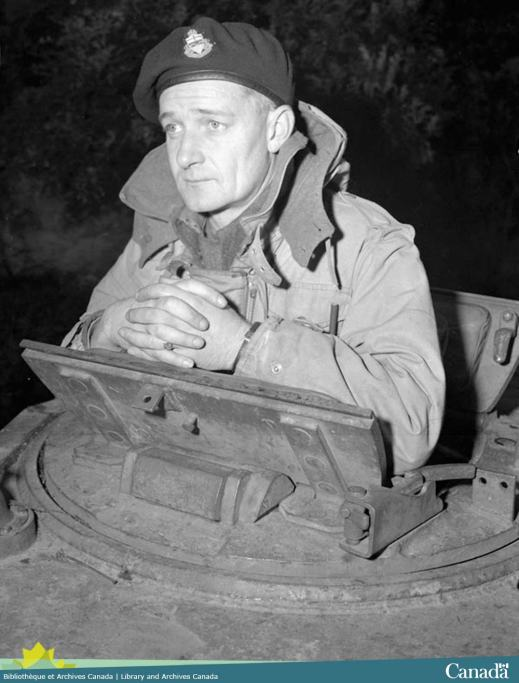 Black and white photograph showing a man peering out over a tank turret.