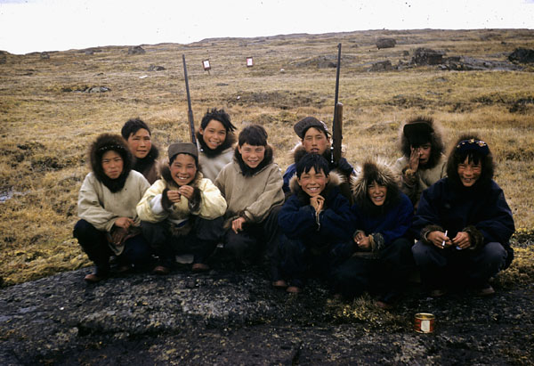 Colour photograph of a group of Inuit boys posing in crouched positions on a large flat rock; two of them are holding rifles