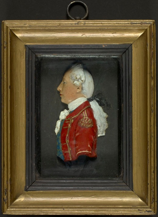Wax miniature, by an anonymous artist, early 19th century. This rather generic wax miniature shows a man in profile wearing a red British coat embellished with gold trimming, a white cravat and a blue waistcoat. He has long white hair, tied back. The miniature is quite sculptural.
