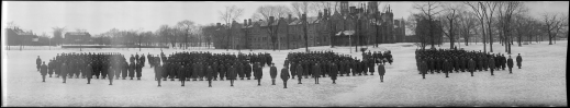 Black and white panoramic photograph of four groups of soldiers standing outside in winter.