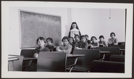 Black and white photograph of Aboriginal girls seated at their desks with a nun standing beside them