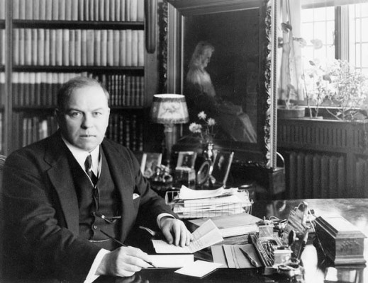 Black-and-white photo of William Lyon Mackenzie King seated at a desk and prepared to sign papers