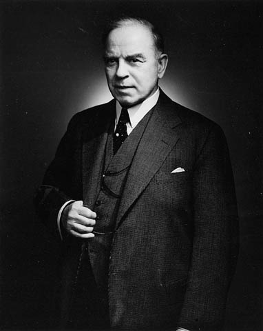 Black-and-white photo of W.L. Mackenzie King standing and holding the lapel of his suit jacket with his right hand