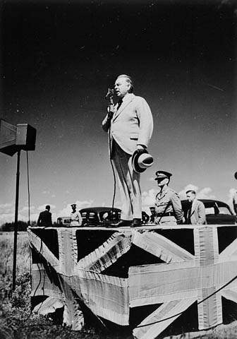 Black-and-white photo of a man speaking through a microphone and standing on a podium that is decorated with the flag of Great Britain