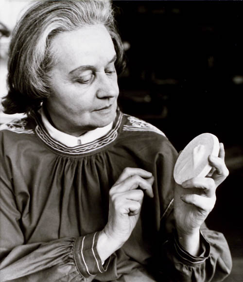 Black-and-white photograph of a woman holding a ceramic model of a medal and looking at it intently.