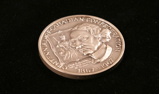 Colour photograph showing a a coin with the image of John A. Macdonald on it with a portrait of a queen behind it.