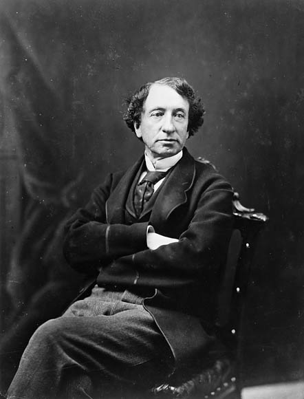 Black and white photograph showing Sir John A. Macdonald sitting on a chair, both his legs and his arms are crossed.