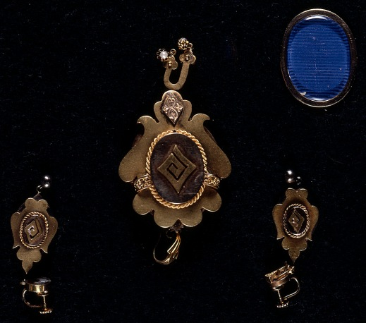Colour photograph of two gold earrings with a stylized spiral pattern and a matching pendant.