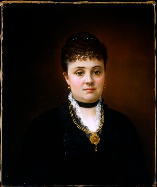 Oil painting showing a woman in a black dress looking straight at the viewer. She is wearing the same pendant and earrings as shown in the previous photograph.