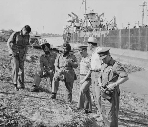Black-and-white photograph of six men standing on the seashore, with a ship visible in the background.