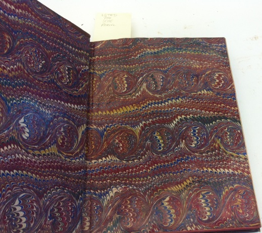 Colour photograph of an open book showing a sumptuous marble paper used for the end paper.
