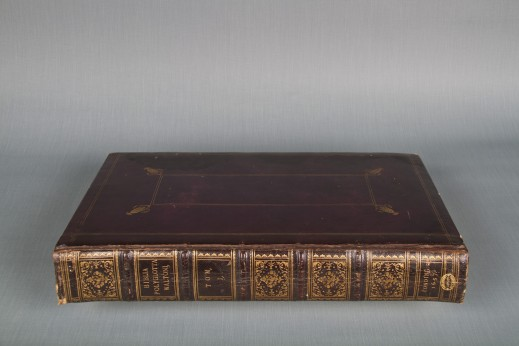 "Colour photograph of a richly ornate book with gold leaf and the inscription ""Bibla Polyglotta Walton"" on the spine."