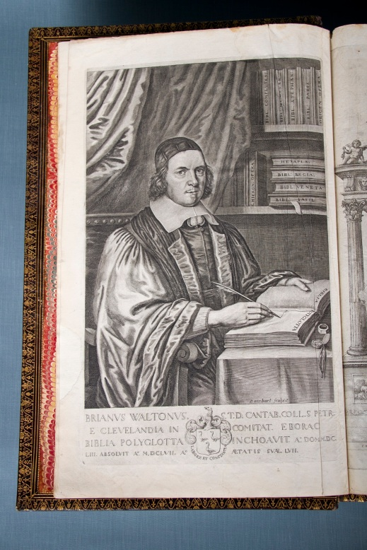 Colour photograph showing an image of a man standing in bishop's robes with a quill in his hand and looking directly at the reader.