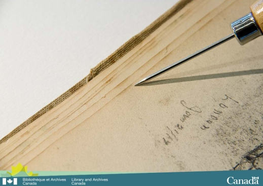 Colour photograph of one side of an open book with its pages fanned out and a pointing device showing the oily stain that is repeated along the edge of each page
