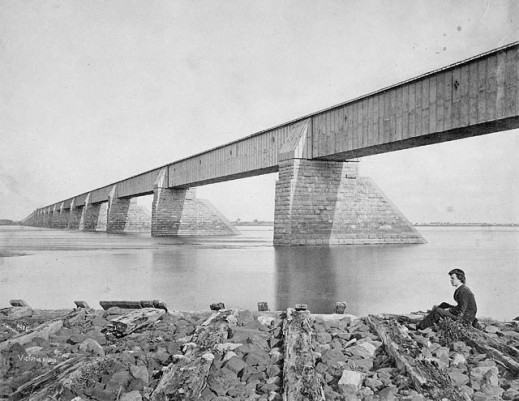 Black-and-white photograph of Montréal's Victoria Bridge, with a young man seated on a rock in the foreground.