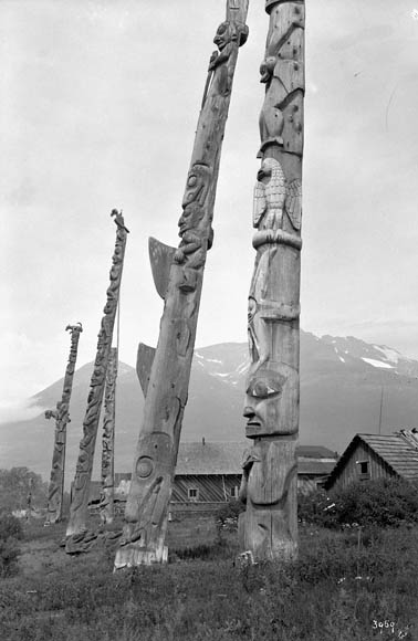 Black-and-white photograph showing five wooden totem poles. In the background are houses and mountains.