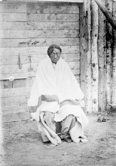 A black-and-white photograph of a man seated, wrapped in a blanket. He is looking directly at the viewer.