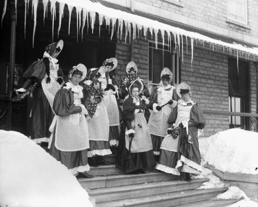 Black-and-white photograph showing eight people standing on a snowy staircase, holding decorative fans. They are all wearing similar costumes comprised of dresses, pinafores and bonnets. Close inspection reveals that some of them have mustaches and look somewhat masculine.