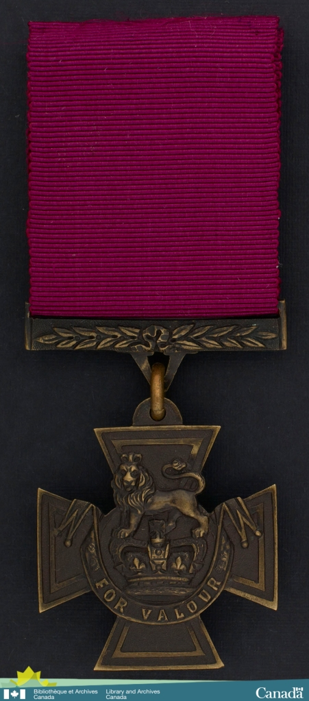 Colour photograph of a medal. Ribbon is crimson. Cross-shaped medal is bronze with a lion above a crown bearing the inscription For Valour on a scroll.