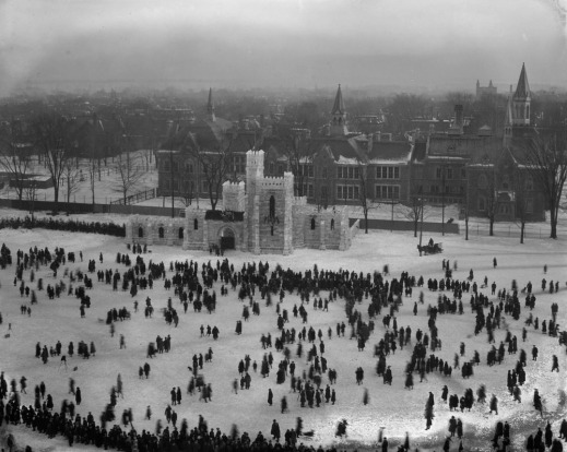 Black-and-white photograph of an ice castle taken from a very high vantage point. Crowds of people are milling about and the city fades into the distance.