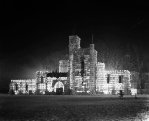 Black-and-white photograph showing an ice castle, brightly illuminated from the inside.