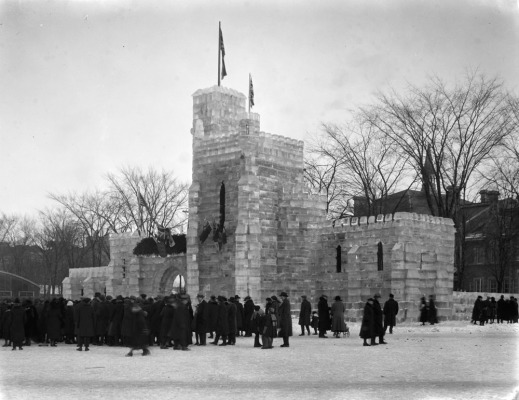 Black-and-white photograph showing many people standing, possibly queuing, around an ice castle.