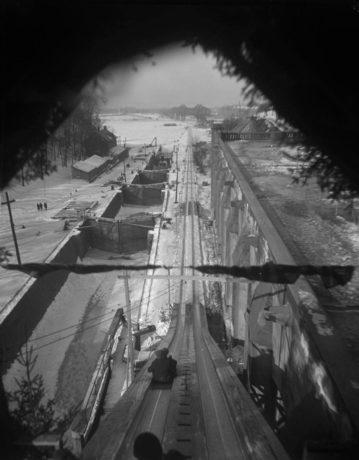 Black-and-white photograph of a view of the toboggan chute looking down towards the river and beside the Rideau Canal Lock. The track is very long and steep, and almost reaches the Alexandra Bridge in the distance.