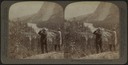 Black-and-white stereograph of two men (one with binoculars) standing on a bluff overlooking Alberta's Bow River.