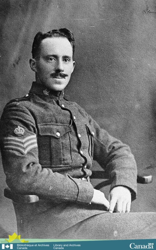Black-and-white photograph of a young soldier, in military uniform, with a moustache sitting in a chair.