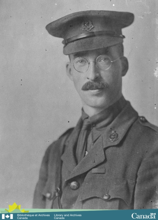 black-and-white photograph showing a young man, in military uniform, with a moustache and glasses looking directly at the photographer.