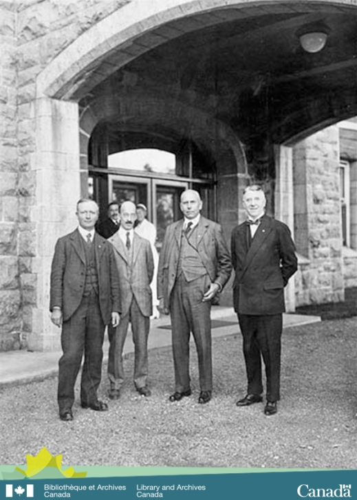 Black-and-white photograph showing four men standing outside the entrance to a building.  In the background, there's a nurse and a man looking on the scene.