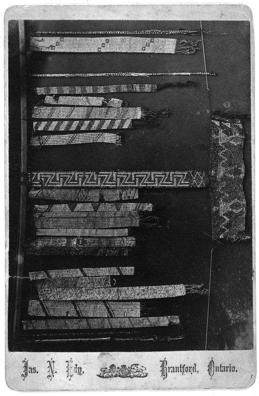 Black-and-white photograph showing several different kinds of wampum belts and strings.