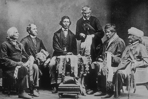 Black and white photo showing six men looking at wampum belts. Five individuals are seated and the sixth seems to be explaining a wampum belt.
