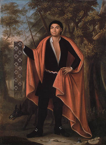 Oil painting on canvas showing a man standing in a forest with a wolf at his feet. He is dressed in black, wearing a red cape, and holding a wampum belt in his hand.