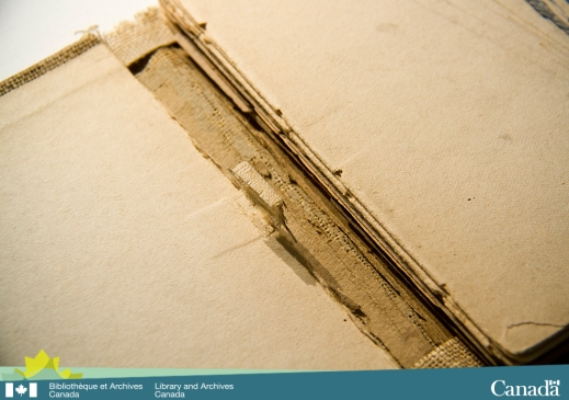 Colour photograph showing the detached spine of a sketchbook. The impression of the sewing tape is clearly visible on both the board paper and on the first page of the folio.