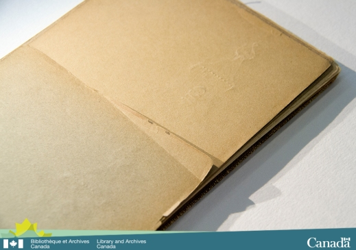 Colour photograph showing a sketchbook that has some deeply indented impressions on one of the pages.