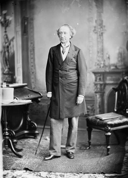 Images show Sir John A. Macdonald wearing an overcoat and standing in various poses on 'set' at Topley Studios, either holding or setting aside a top hat and cane.
